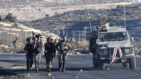 Pracownicy izraelskich służb porządkowych podczas starć na granicy palestyńsko-izraelskiej niedaleko Ramallah - Sputnik Polska