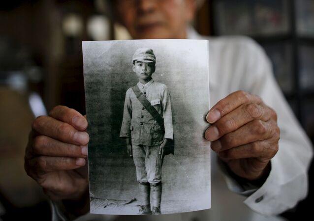 86-letni mieszkaniec prowincji Fukushima Yoshiteru Kohata, który przeżył atak atomowy na Nagasaki, pokazuje swoje szkolne zdjęcie