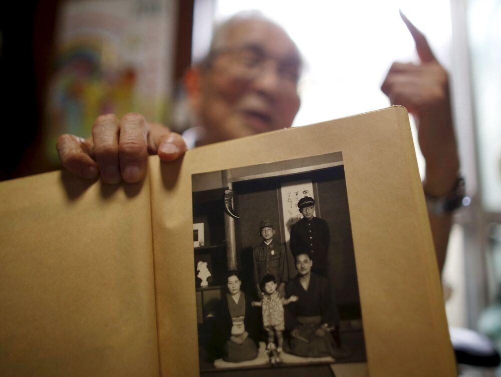 Japoński profesor i były prezydent Uniwersytetu Fukushimy Atsushi Hoshino, który przeżył atak atomowy na Hiroszimę, pokazuje zdjęcie swojej rodziny zrobione w 1941 roku