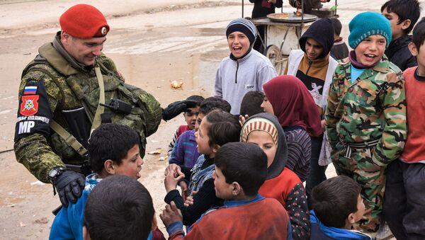Pracownik rosyjskiej policji wojskowej z syryjskimi dziećmi - Sputnik Polska