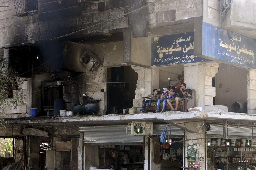 Miezkańcy siedzą na balkonie zburzonego domu w Aleppo