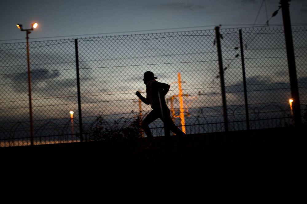 Uchodźca biegnie w kierunku tunelu pod kanałem La Manche w Calais na północy Francji