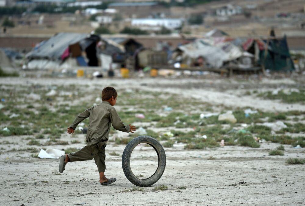 Afgański chłopczyk gra w obozie koczowników w Kabulu