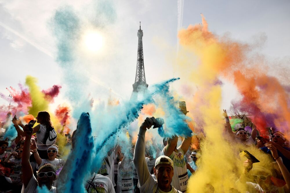 Uczestnicy biegu Color Run 2018 świętują swój finał naprzeciw wieży Eiffla w Paryżu