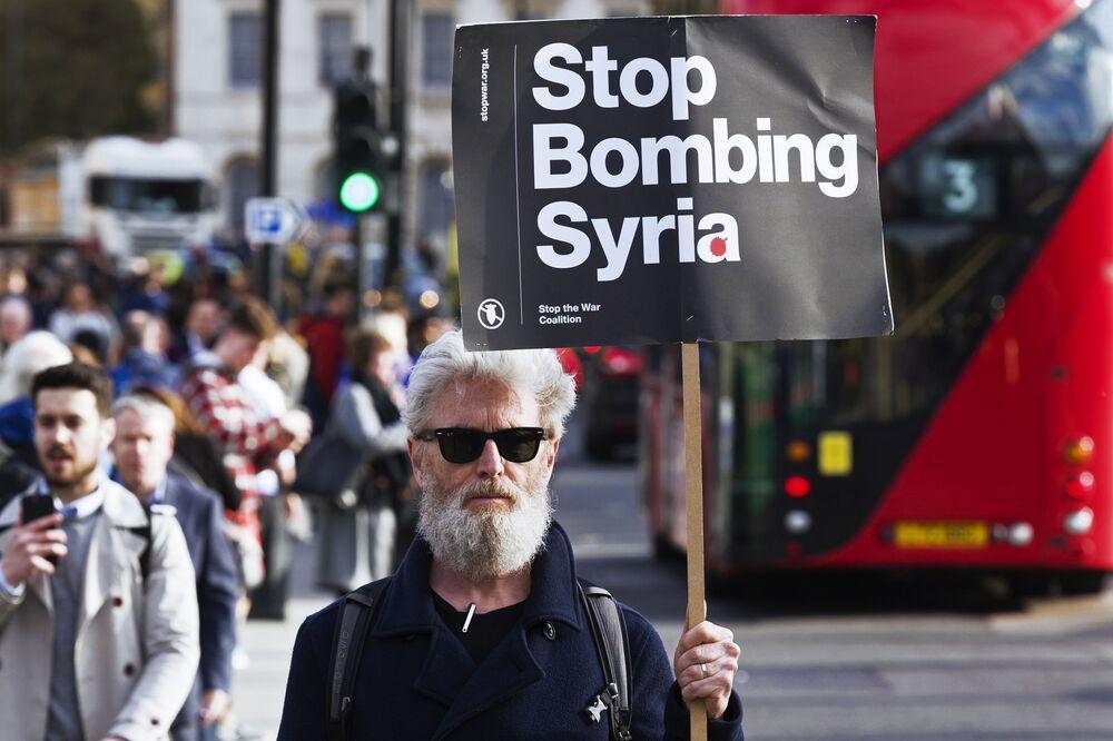 Mężczyzna trzymający transparent wzywający nie bombardować Syrii, na akcji protestu przeciwko atakom na Syrię w Londynie