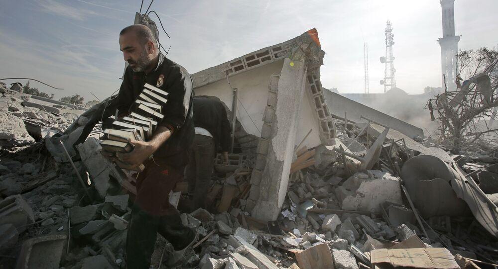 Mężczyzna wynosi Koran z ruin budynku w Gazie