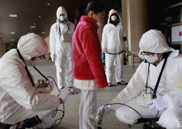 Dozymetrysta sprawdza ludzi w Fukushimie.