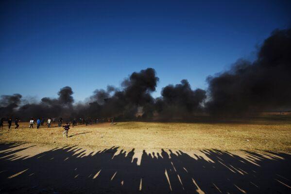 Palestyńscy demonstranci podczas starć z izraelskim wojskiem na granicy Strefy Gazy z Izraelem - Sputnik Polska