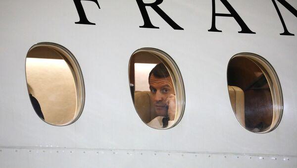 Prezydent Francji Emmanuelle Macron podczas rozmowy telefonicznej w samolocie - Sputnik Polska