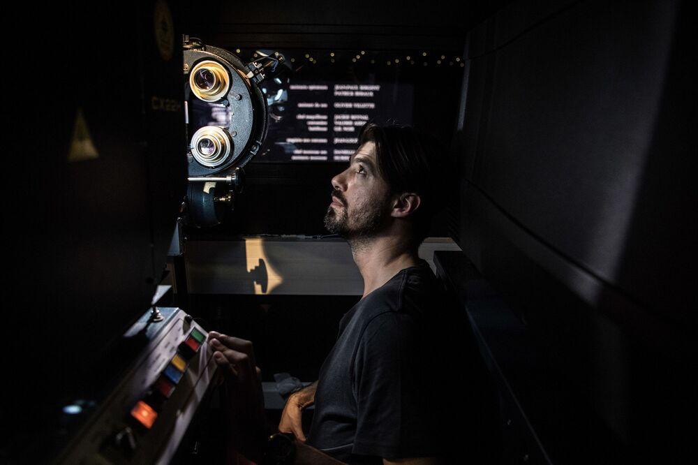 Kinooperator Benjamin Louis sprawdza wyświetlenie filmu analagowego w kinie Louxor. Paryż, Francja
