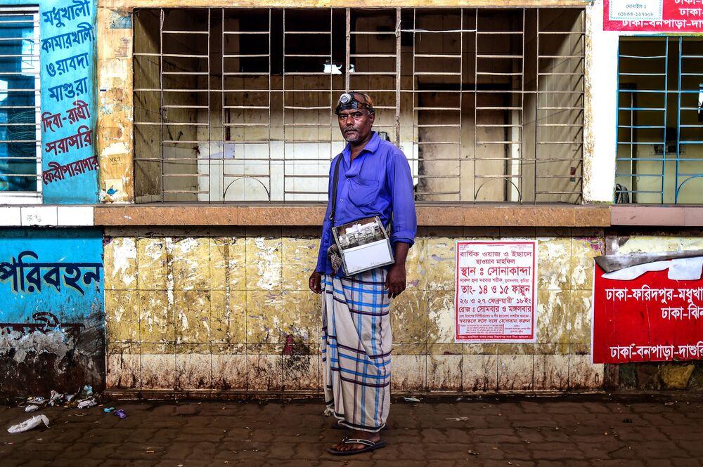 Czyściciel uszu Mohammad Joynal stoi na ulicy, gdzie pracuje. Dhaka, Bangladesz