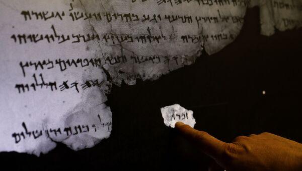 Pracownik Israel Antiquities Authority pokazuje na ultraczerwone skanowanie fragmenty zwoju z Morza Martwego - Sputnik Polska