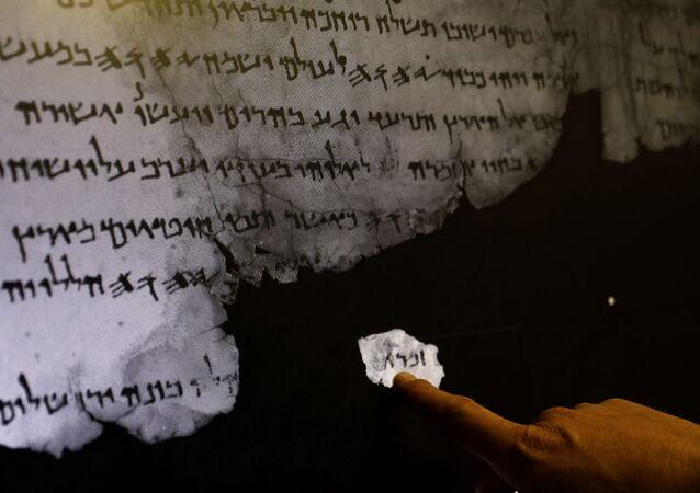 Pracownik Israel Antiquities Authority pokazuje na ultraczerwone skanowanie fragmenty zwoju z Morza Martwego
