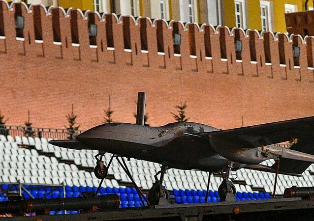 """Pierwszy w Rosji szturmowy samolot bezzałogowy """"Korsar"""" podczas przejazdu sprzętu wojskowego, który weźmie udział w paradzie wojskowej na Placu Czerwonym"""