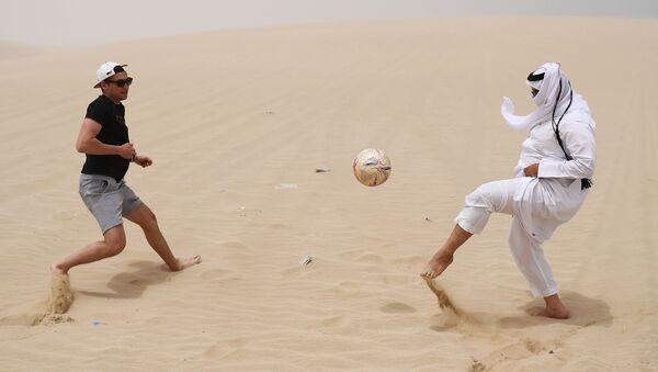 Mężczyźni grają w piłkę nożną na pustyni Khor Al Adaid. Doha, Katar - Sputnik Polska