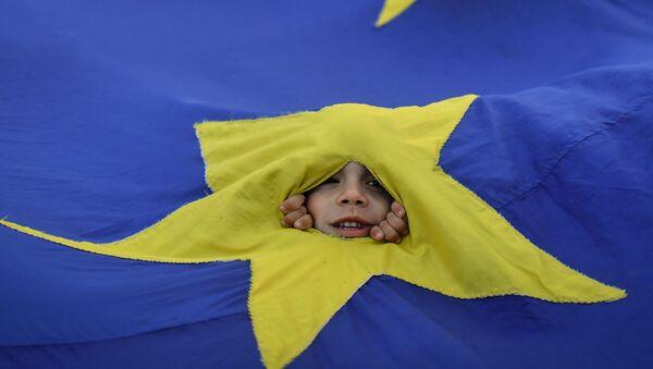 Chłopiec wyglądający spoza flag UE w czasie demonstracji w Bukareszcie - Sputnik Polska