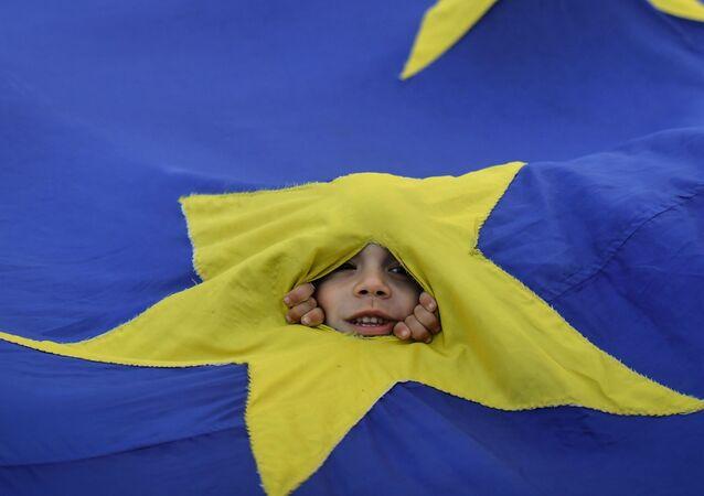 Chłopiec wyglądający spoza flag UE w czasie demonstracji w Bukareszcie