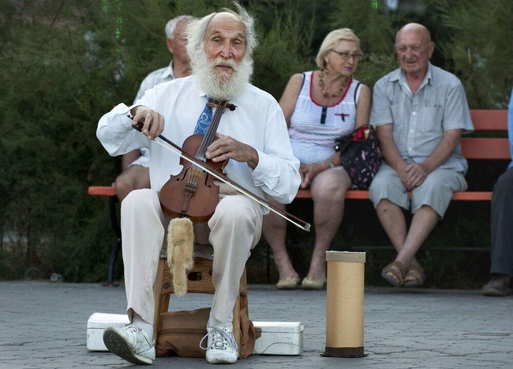 Muzyk gra na skrzypcach na nabrzerzu na Krymie