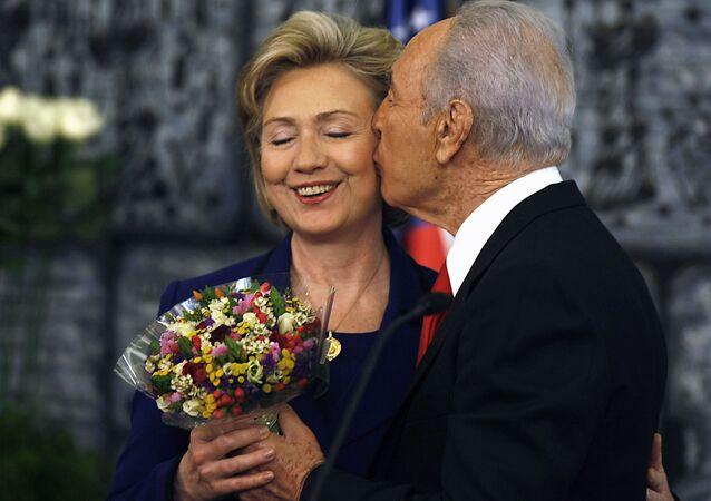 Prezydent Izraela Shimon Peres całuje Hillary Clinton i wręcza bukiet kwiatów po konferencji prasowej w Jerozolimie, 2009 rok