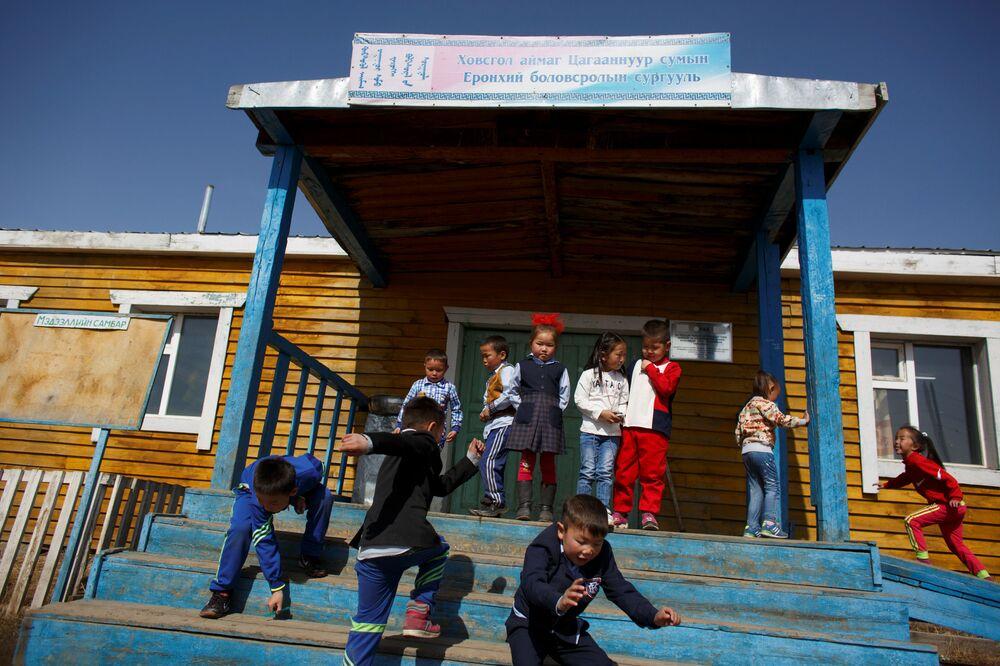 Uczniowie miejscowej szkoły wychodzą na ulicę po lekcjach we wsi Cagaannguur, Huvsgel, Mongolia