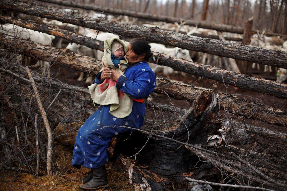 Mongolska kobieta kołysa dziecko na rękach