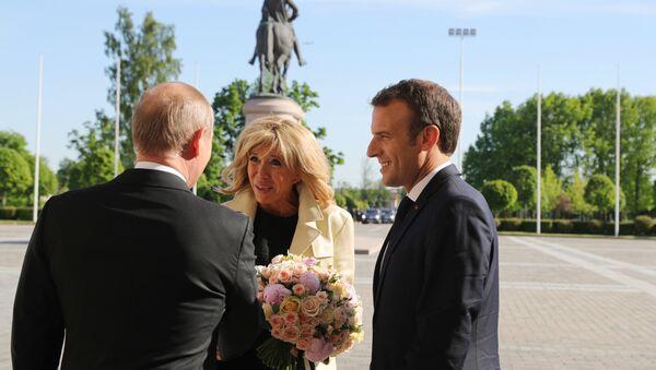 Władimir Putin wręcza bukiet kwiatów żonie Emmanuela Macrona Briggite Macron - Sputnik Polska