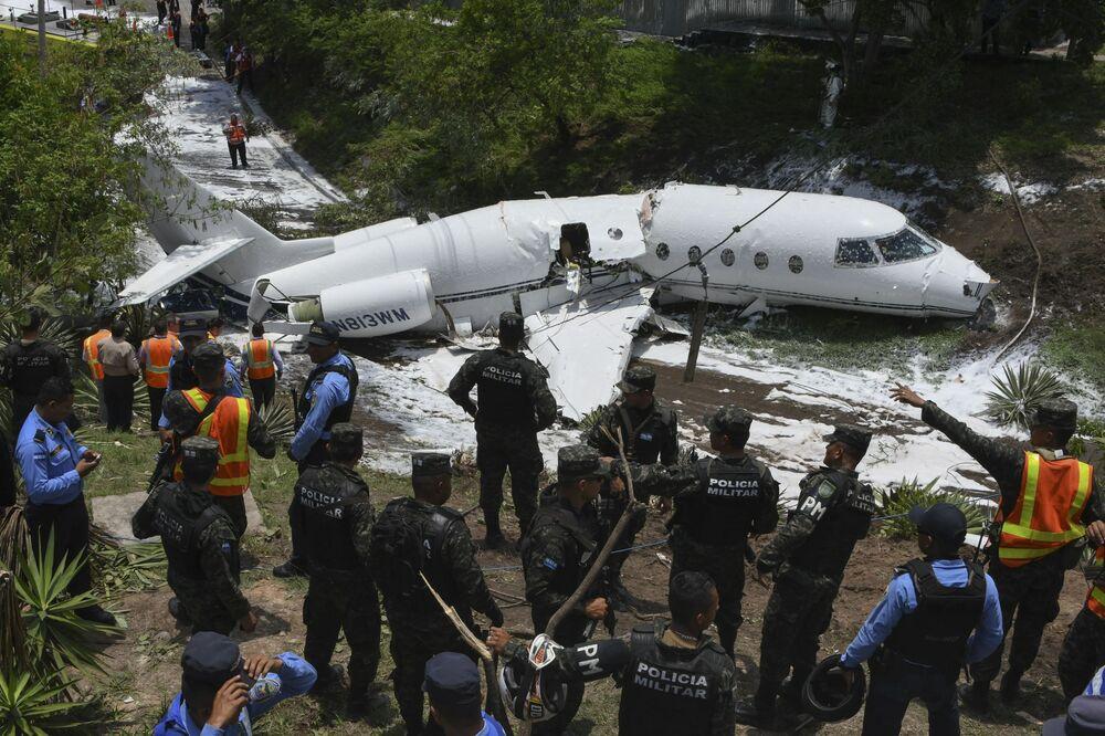 Policja i ratownicy pracują koło samolotu, który wytoczył się z pasa startowego i rozpadł się po wylądowaniu na lotnisku Tonkontin w Tegucigalpa w Hondurasie
