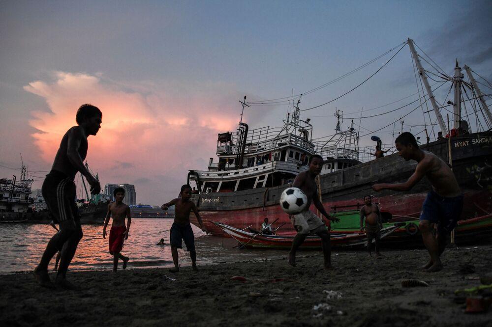 Młodzi ludzie grają w piłkę nożną na brzegu rzeki Yangon w mieście Yangon, Myanma