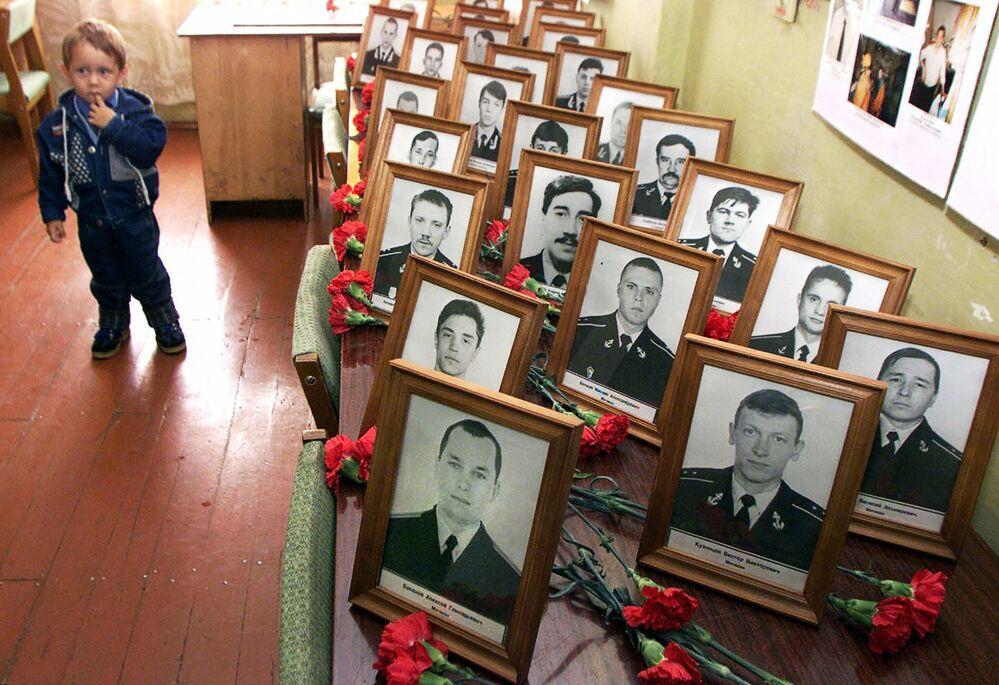 Chłopczyk stoi przy portretach członków załogi zatopionego okrętu podwodnego Kursk podczas ceremonii żałobnej