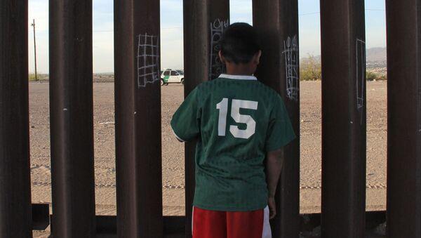 Chłopczyk u ogrodzenia na meksykańsko-amerykańskiej granicy - Sputnik Polska