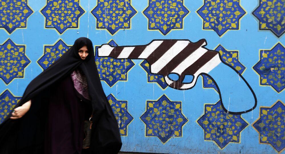 Iranka na tle graffiti pod byłym budynkiem ambasady USA w Teheranie