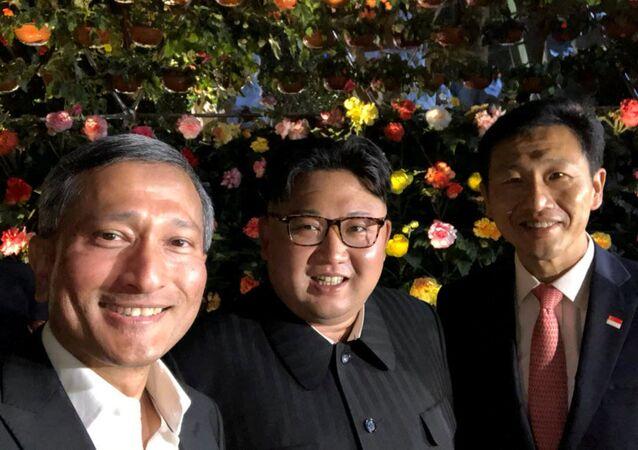 Szef MSZ Singapuru Viviana Balakrishnana zrobił sobie selfie z Kimem i jeszcze jedną osobą, na tle kwiatów