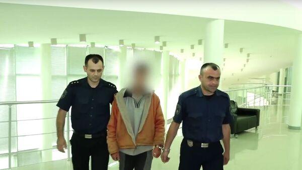 Kadr z wideo, na którym policjanci konwojują podejrzanego o zabójstwo amerykańskiej rodziny w Wąwozie Hada - Sputnik Polska