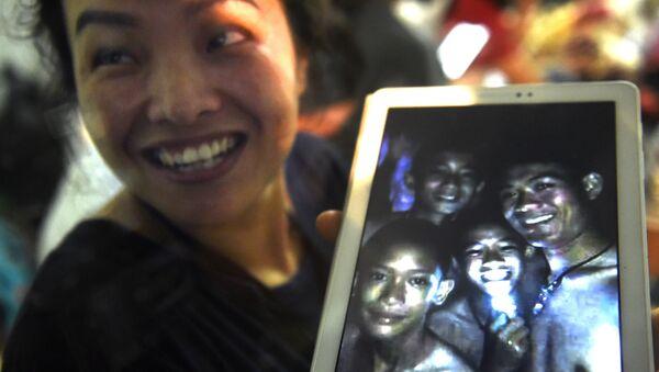 Mama jednego z 12 chłopców zaginionych w jaskini Tham Luang pokazuje zdjęcie swojego syna i trenera jego drużyny piłkarskiej Ekkapola Chantawonga - Sputnik Polska