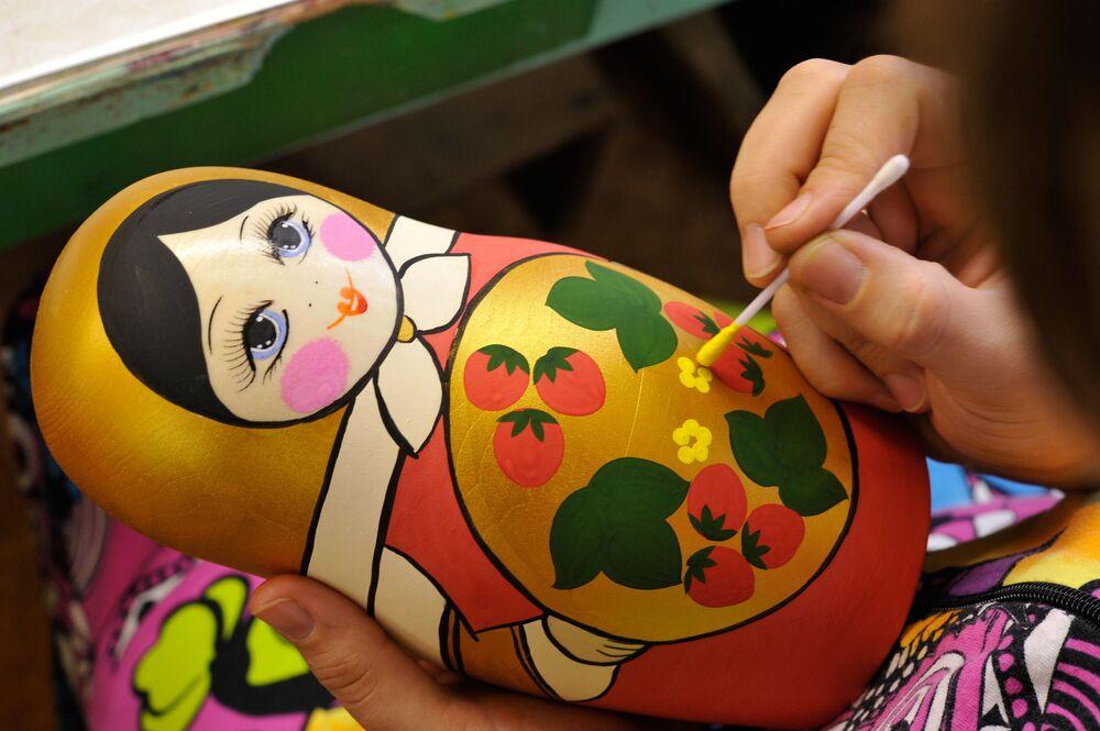 """Pracownica stowarzyszenia artystycznego """"Chochłomska rozpis"""" malująca matrioszki w zakładzie przedsiębiorstwa"""