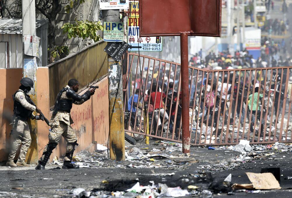 Policjant używa broni podczas akcji protestacyjnej na Haiti