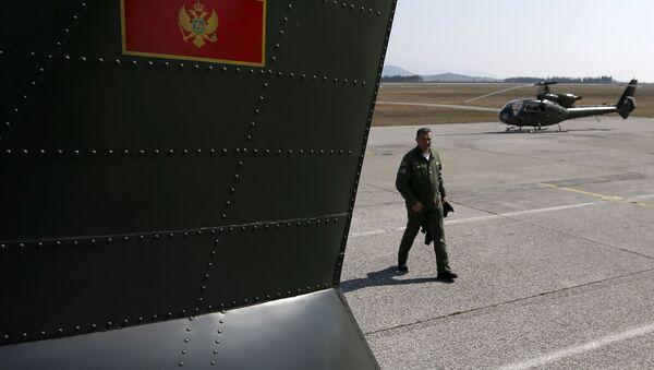 Czarnogórski żołnierz obok śmigłowców wojskowych na lotnisko Podgoricy - Sputnik Polska