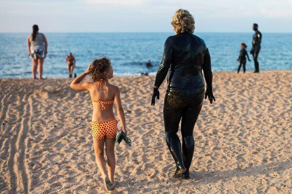 Kąpiele błotne na Krymie (Jezioro Czokrak), kobieta idzie wykąpać się w morzu - Sputnik Polska