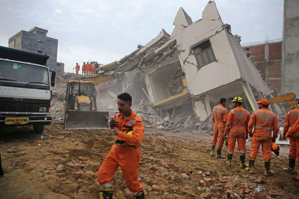 Ratownicy pracują na miejscu zawalenia się budynku, Indie