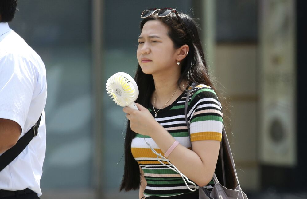 Dziewczyna z kieszonkowym wentylatorem podczas anomalych upałów w Tokio