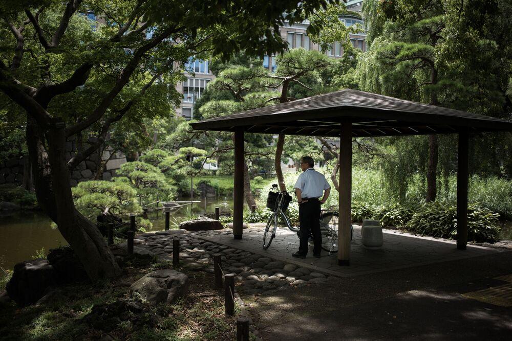 Mężczyzna odpoczywa w zacienionym miejscu parku podczas anomalnych upałów w Tokio