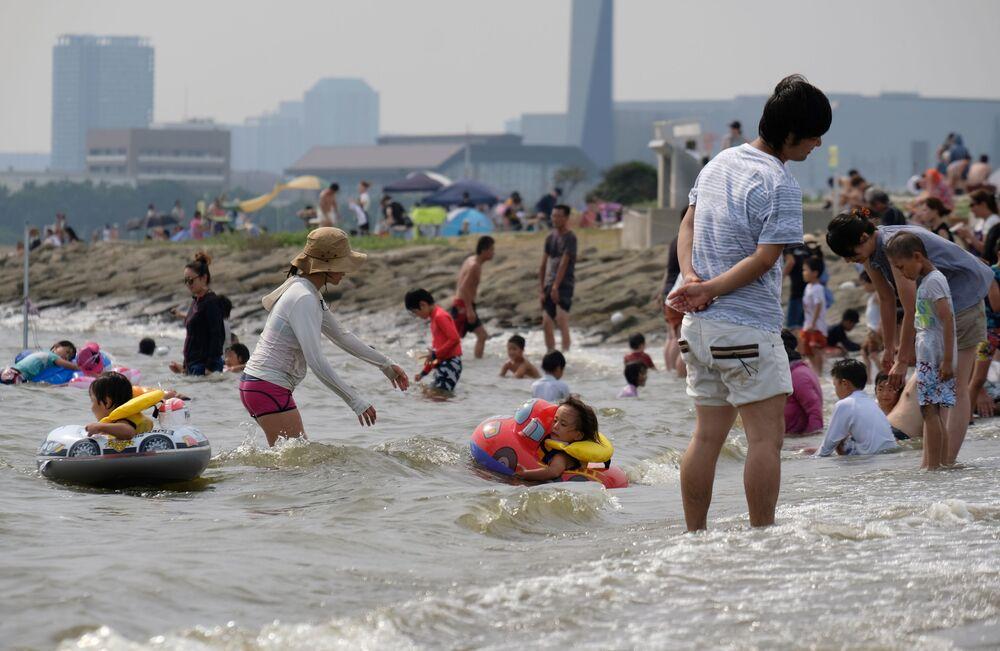 Ludzie z dziećmi kąpią się podczas anomalnej pogody w Tokio