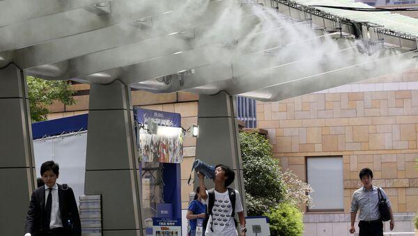 Ludzie pod ochładzającym urządzeniem podczas anomalnych upałów w Tokio - Sputnik Polska