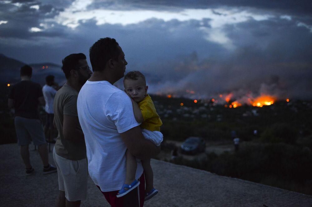 Mężczyzna z dzieckiem w ramionach patrzy na pożar niedaleko Aten