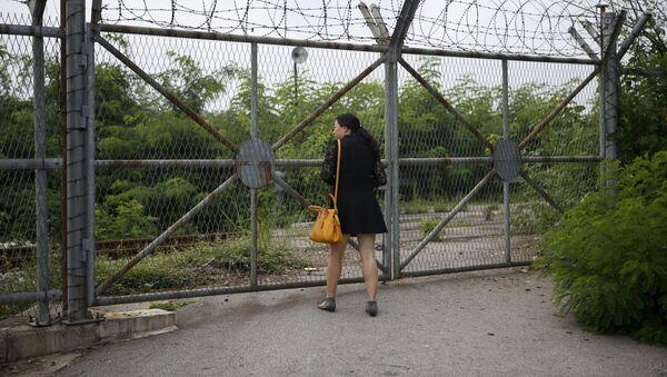 Chińska turystka patrzy przez ogrodzenie około strefy zdemilitaryzowanej pomiędzy Koreą Północną a Koreą Południową - Sputnik Polska