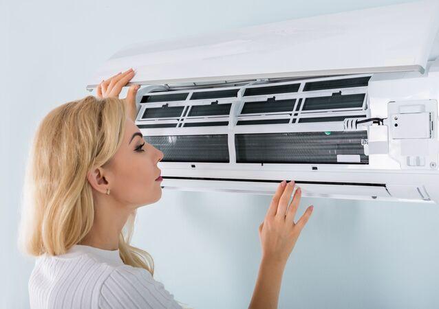Kobieta przy urządzeniu klimatyzacyjnym