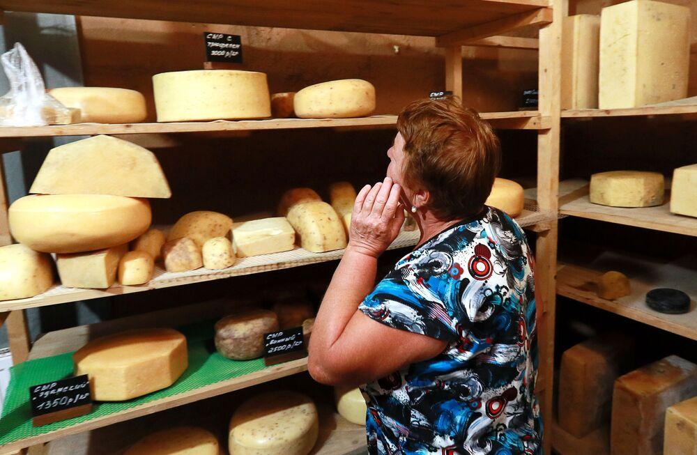 Kobieta wybiera ser w sklepiku przy farmie