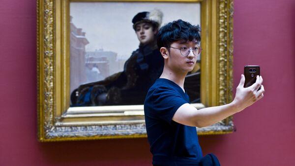 Odwiedzający wystawę fotografuje się przy obrazie Iwana Kramskogo «Nieznajoma» - Sputnik Polska