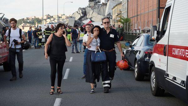 Strażak prowadzi płaczącą kobietę z miejsca tragedii w Genui - Sputnik Polska