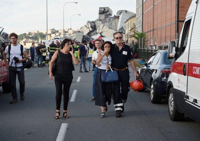 Strażak prowadzi płaczącą kobietę z miejsca tragedii w Genui
